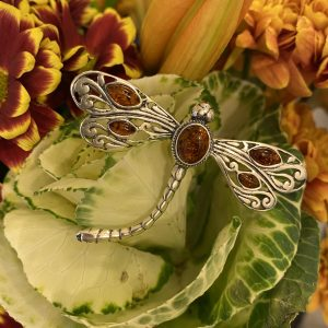 amber dragonfly brooch on flowers